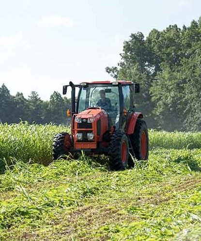 Red tractor plowing a field